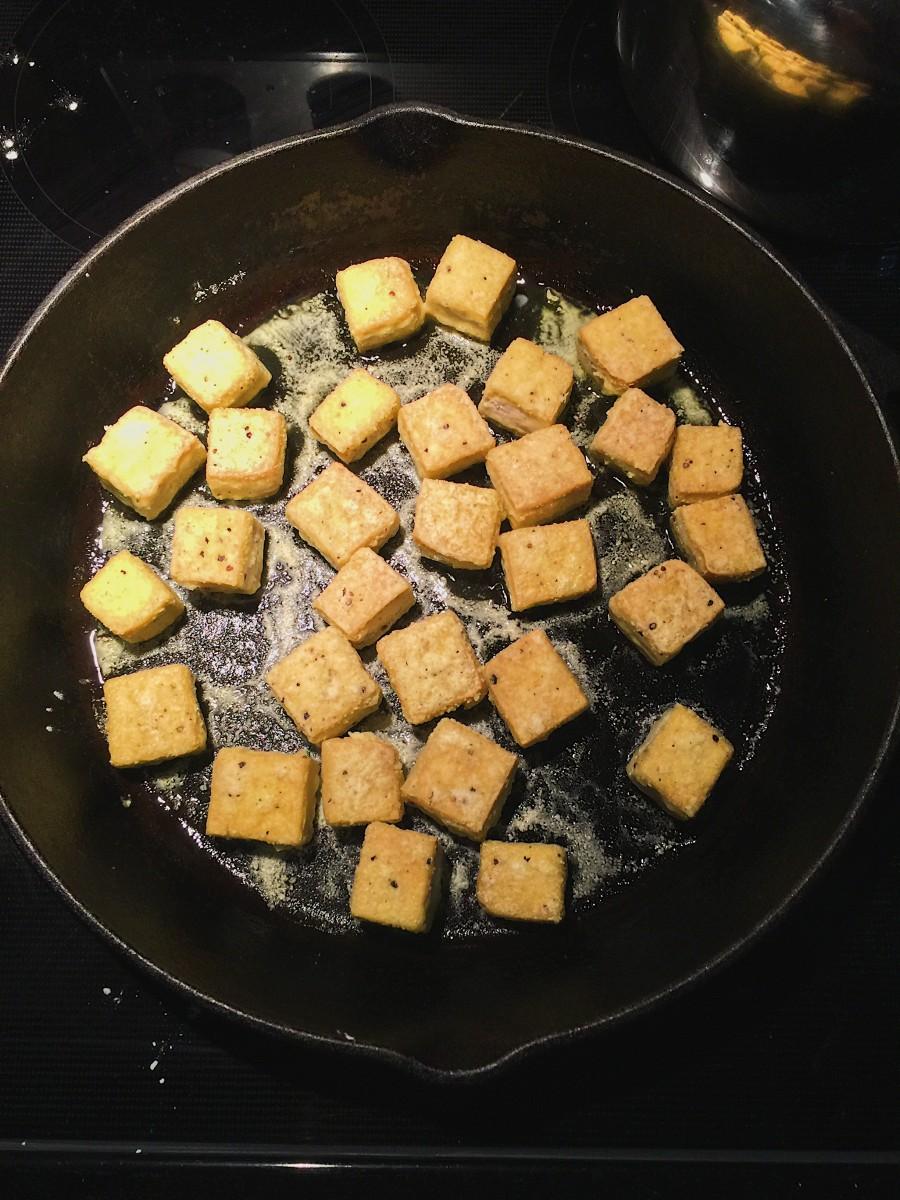 Tofu browning in a pan